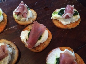 Hors d'oeuvres: crostini topped with ricotta, chive oil, spinach and prosciutto.
